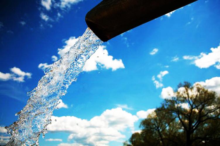 Água saindo de um tubo sob céu azul