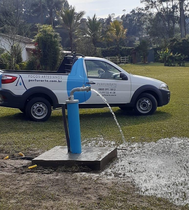 Poço artesiano jorrando água e carro da Perfurarte atrás