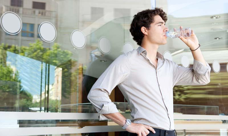 Empresário jovem bebendo água em escritório