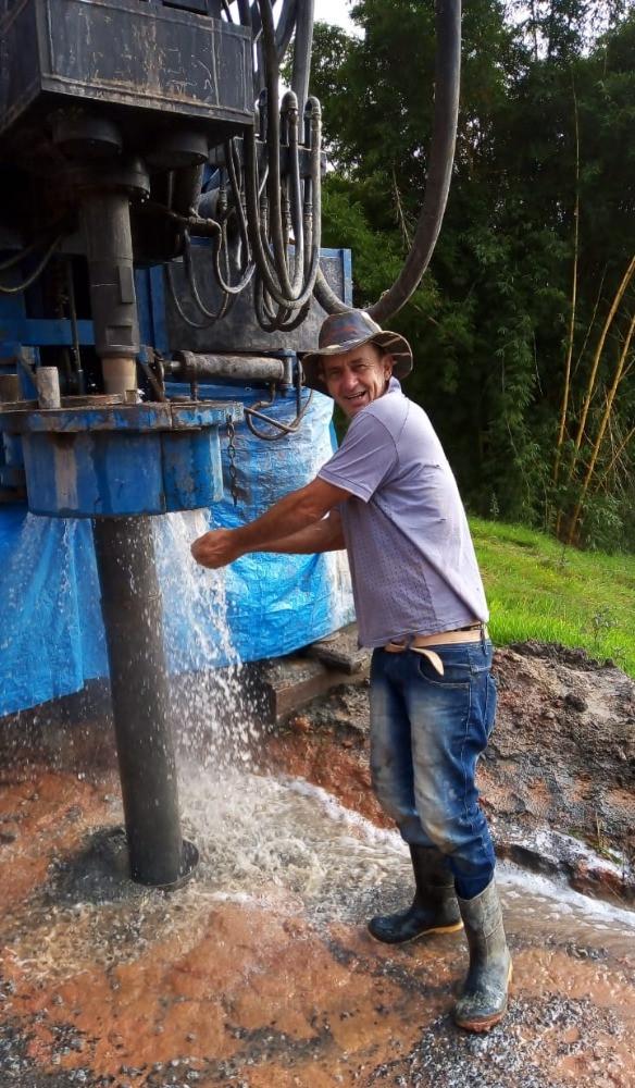 Cliente satisfeito ao lado de poço perfurado que deu água
