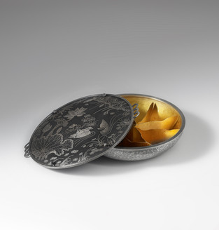 """""""One Fine Day."""" Nine-section dry-food container. 2016. Jjoeum ipsa and ottchil, raising, forming, texturing, casting lily flower buds as prongs, Korean damascene on mild steel, setting, constructing, oxidizing, sumac ottchil coating finish. Fine and sterling silver, mild-steel. 8"""" x 27"""" x 25""""."""