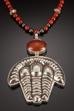 "Trilobite-Scape. 1994. Pendant. Silver, carnelian beads, hermatite beads. 20"" x 4"" x 0.5""."