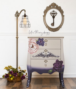 Single bombay nightstand painted in Dixie Belle Paint Company French Linen and Aubergine. Moonshine Metallic Silver Bullet was used to highlight the #woodubendmoulding appliques that were added to the drawer front and feet. #redesignwithprima Decor Transfer Lush Floral II was used to create a flower motif