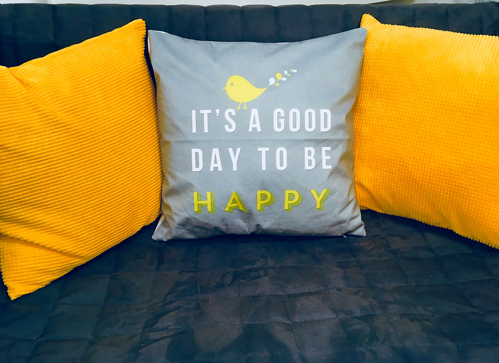 "Yellow cushions, one says ""it's a good day to be happy"""
