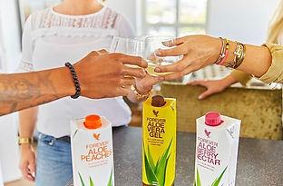 cilvēki saskandina glāzes ar alvejas sulu