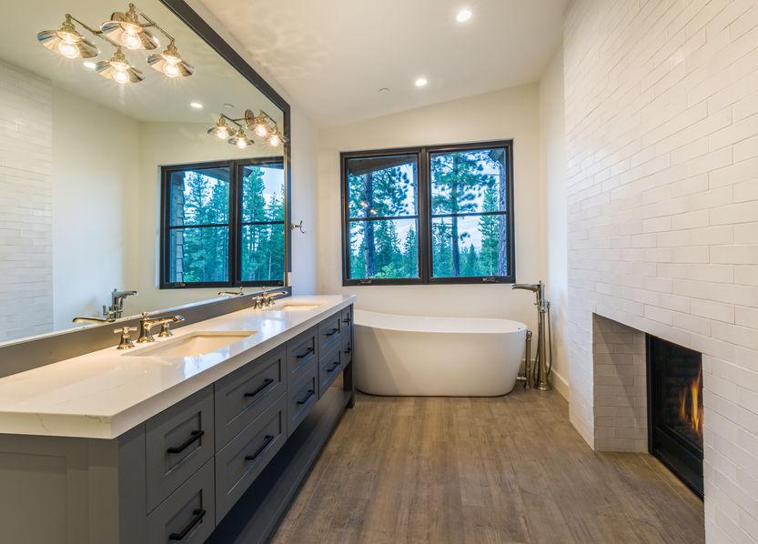 Main bathroom of modern cozy home, fireplace in bathroom, soaking tub