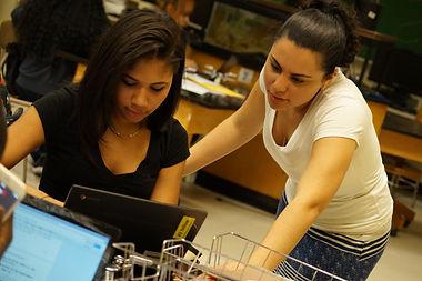 teacher helping student at laptop