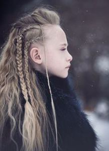 Image of a young girl with long blonde braided hair wearing a black winter fur like coat in a snow setting