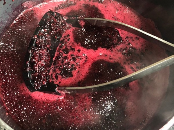 Elderberries being mashed during preparation for jelly making