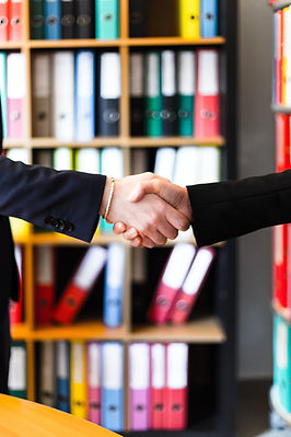 two-person-handshakes-in-front-of-books-
