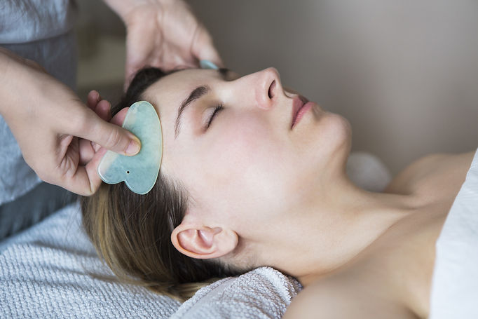 Young woman have face guasha treatment a