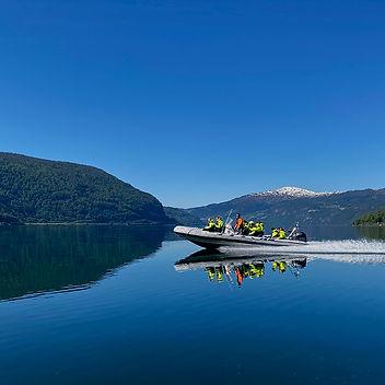 RIB båt på Nordfjorden med utsikt over fjell, fosser og smaragdfgrønt vann