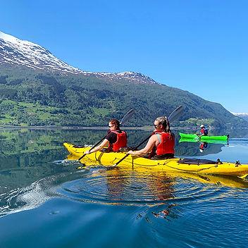Kajakkpadling på Nordfjord med utsikt over fjell, fosser på smaragdgrønt vann