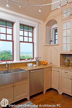 The stainless steel farm sink shares the counter with a tiny arch-topped appliance garage.