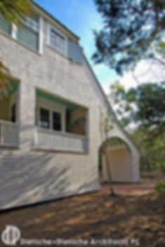 The Shingle Style roof slopes to create an intimate arched entry to the back garden.