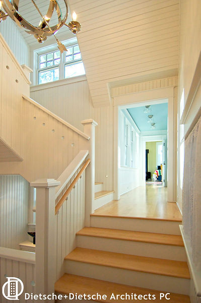 At Cottage on a Lake, the white bead board stairway opens directly into the living spaces.