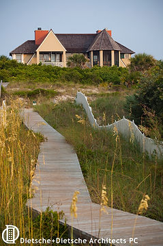 Balanced asymmetrical porches are visible from the winding boardwalk to the beach.