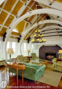 The Whale Cottage main room is spanned by arching white ribs with a vaulted open-construction ceiling above