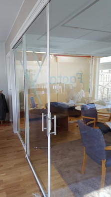 Toimiston lasiseinä ja ovi. Valoisa ratk