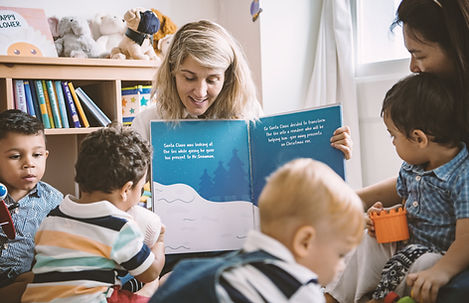 Women reading a story book to children