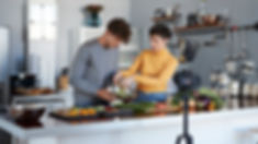 Man and woman cooking in front of a camera