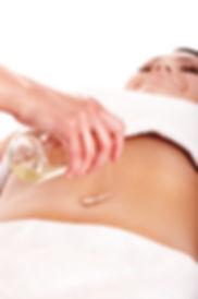 Vrouwenhand laat uit een flesje langzaam massageolie in de navel van een vrouw vloeien