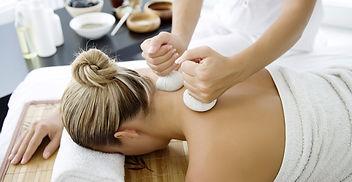 Vrouw ligt op de buik en ontvangt een kruidenstempel massage