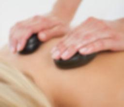 Vrouwenhanden masseren de bovenrug van een blonde dame met 2 zwarte hotstone massagestenen