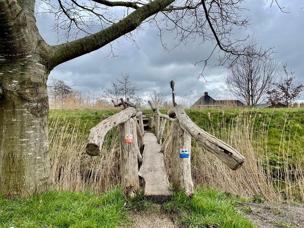 Klompenpad Kopermolenpad: akkers, molens en beken De tijd lijkt even stil te staan in Wenum Wiesel. Een wandelroute langs akkers, hooiland en beken. Rust en stilte op open landbouwgronden.  Wind in de haren, een modderig pad en dreigende wolken.  Het 13 kilometer lange Klompenpad 'Kopermolenpad' ligt ten noorden van Apeldoorn en verrast ons in al haar eenvoud.   Start van Klompenpad Kopermolenpad We beginnen het Kopermolenpad bij restaurant Gewoon Gastvrij, Elburgerweg 1 in Wenum Wiesel. Daar parkeren we de auto en volgen we de oranje markering in de vorm van een klompje. We worden al snel omringd door weiland. Het malse gras, de knopjes in de bomen en een witte pony die ons begroet, zorgen ervoor dat we vrijwel direct ontspannen. Lekker wandelen door een onontdekt stukje Nederland.   Langs de Wenumse Beek Een hekje door, een paadje in en niet veel later lopen we langs de Wenumse Beek. De Wenumse Beek is (voor het grootste deel) een kunstmatig aangelegde beek. Het water komt van sprengen, regen- en kwelwater. Vroeger stonden er vijf molens aan de beek. Nu is alleen de Wenumse watermolen nog over, en die zien we al snel verschijnen aan het eind van ons pad.   Rijksmonument Wenumse watermolen De watermolen van Wenum ligt aan een smalle oude weg. De Wenumse Beek stroomt er langs en aan de overkant van de weg mondt de beek uit in een waterplas. Oorspronkelijk was het een korenmolen, maar in 1768 werd het een kopermolen en werden er koperen platen geslagen. De Wenumse watermolen is een rijksmonument. Langs de molen wandelen we verder via één van de zo typische houten 'klompenpadbruggetjes'.   Oranjemolen in de verte De route gaat verder via smalle paadjes door het weiland waar we doorheen struinen. Als we weer op de verharde weg komen, zien we de Oranjemolen al liggen in de verte.  Eenmaal aangekomen bij de molen blijven we even staan om het bouwwerk te bewonderen. Het jonge melkvee aan de overkant van de weg is ook blij met een verzetje kijkt ons nieuwsgierig aan.    De