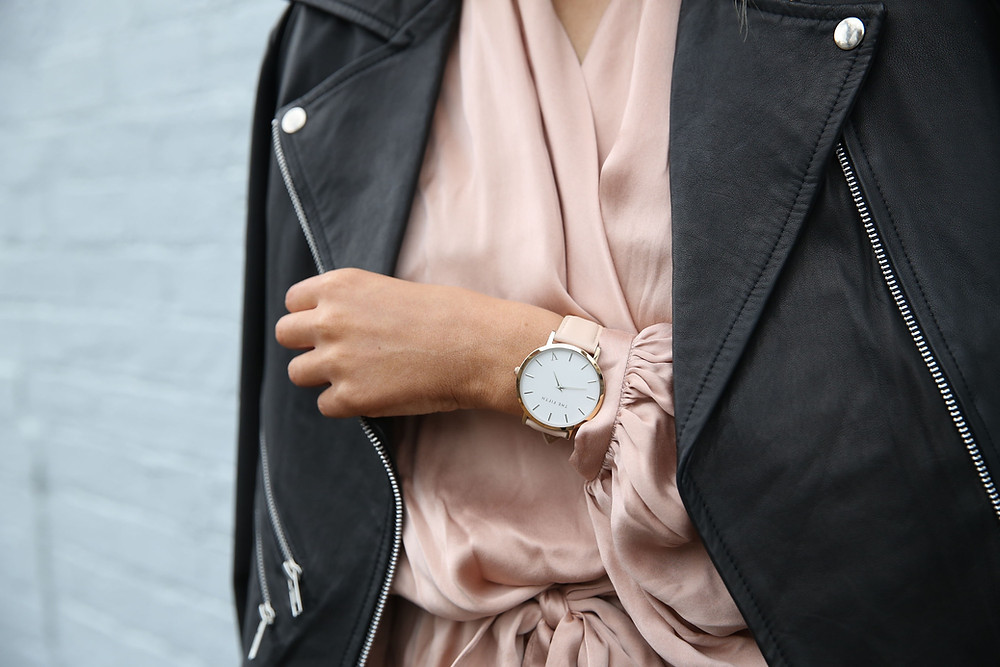 blush pink silk blouse with large minimal watch and black biker jacket