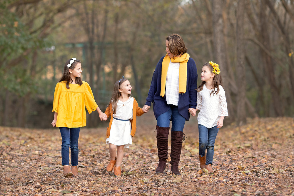 outdoor fall portrait of a mom walking with her daughters