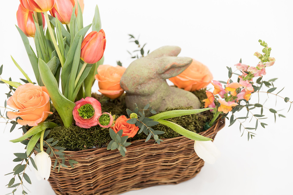 a centerpiece arranement with fresh cut flowers, hardgoods, basket, and tulips