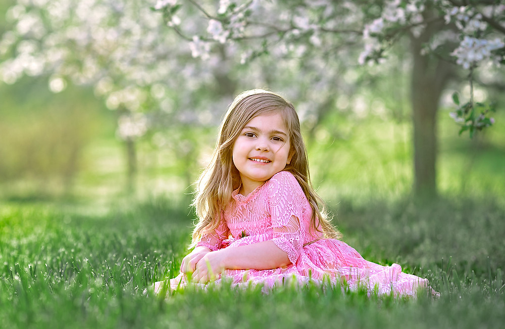 a young girl posing in a blooming apple orchard