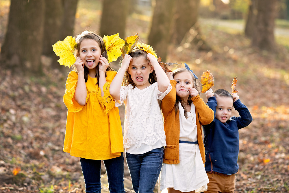 outside portrait of children being goofy with autumn leaves