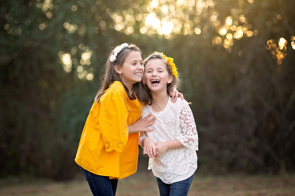 outdoor portrait of two sisters laughing