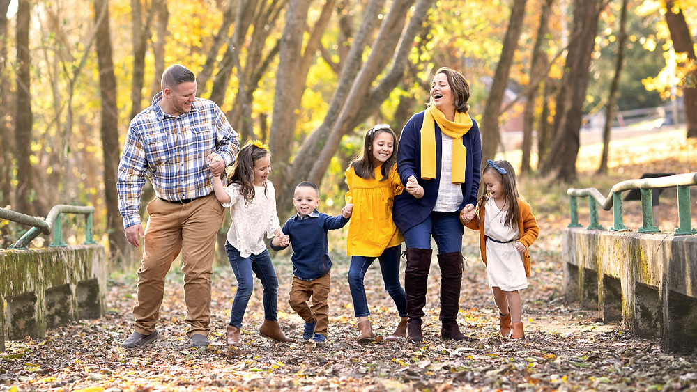 outdoor autumn portrait of a family laughing together