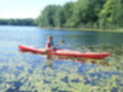 Jane Banning in a red kayak surrounded by lily pads
