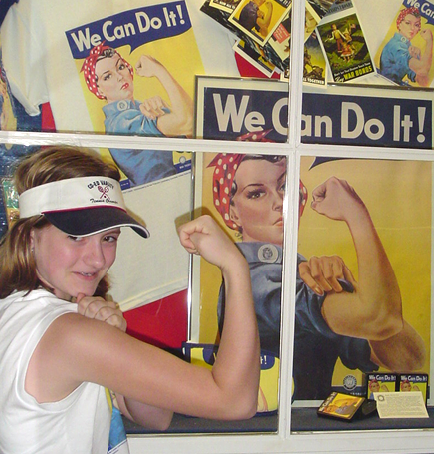 Rhiley Binns long before she was a doula, posing with Rosie the Riveter posters on a family trip.