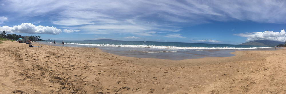 A panorama sandy beach in Maui, Hawaii.  There are thin clouds in a blue sky and waves are rolling in.