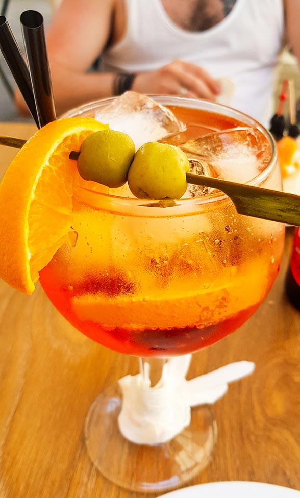 Sangria cocktail on ice with olive orange trimmings