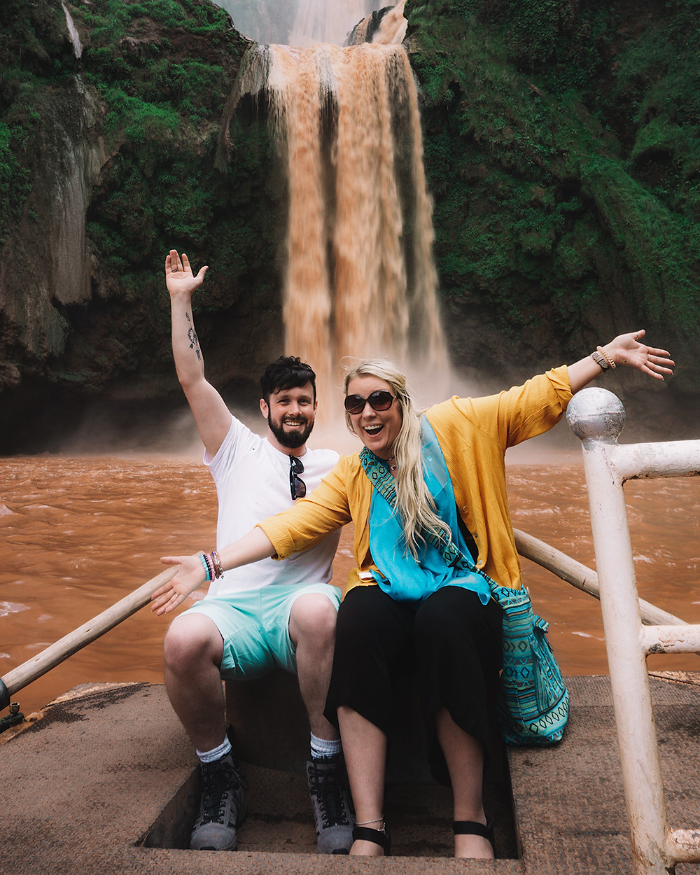 Couple smiling in front of Ozoud Waterfalls Morocco