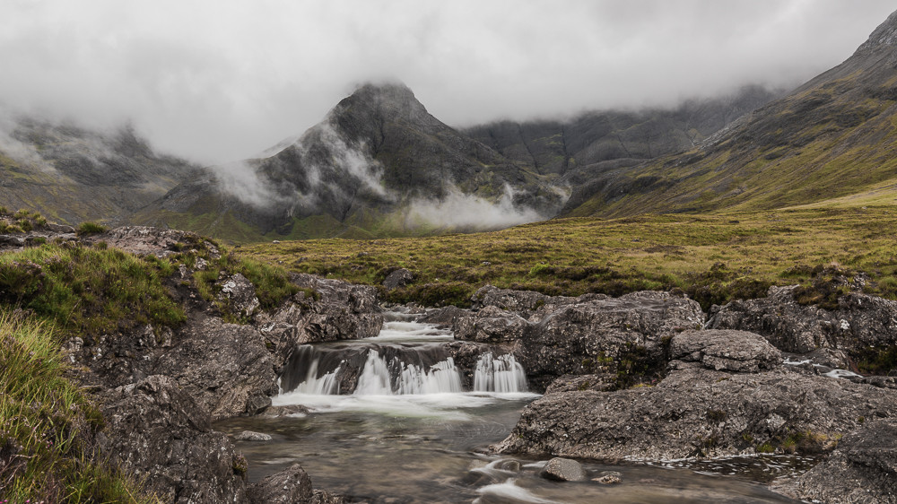 small waterfall with misty mountains