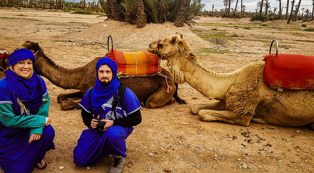 man and woman with camera sat by camels