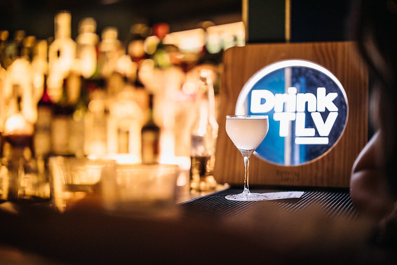 a cocktail in a bar with a drink tlv light