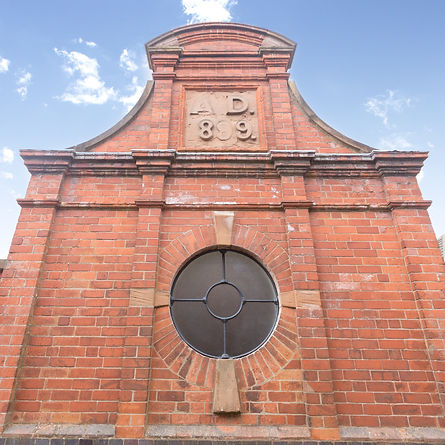 A picture showing the gable end of our Kimberley Brewery Development. Reclaimed brickwork with a round window.