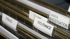 Folders of insurance fraud cases. ICU Investigations. Private investigator near me.