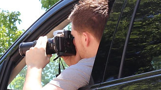 Private investigator with camera leaning out of car. Surveillance. ICU Investigations.