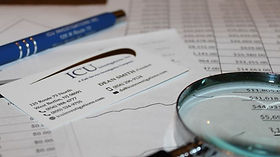 Financial documents and magnifying glass. Asset Investigations. Private investigator near me.