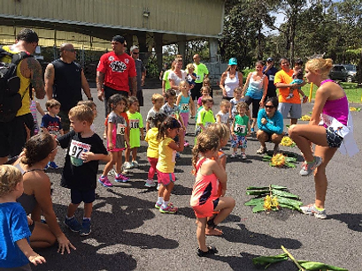Photo of Guinevere Davenport warming up with the children before the Volcano Rain Forest Run. Photo Courtesy of the Volcano Rainforest Run.