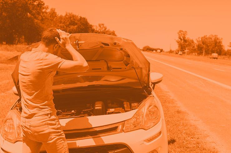 Homem jovem segurando celular em frente a um carro com problema